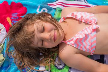 enfant sur sa serviette de plage