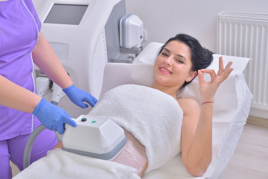 Beautiful young woman getting cryolipolyse fat treatment in professional cosmetic cabinet