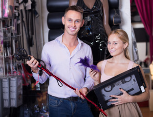 Happy adult couple choosing sex accessories in shop