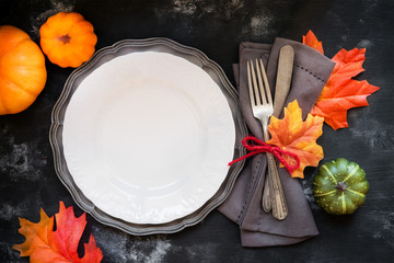 Autumn or Fall table place setting with vintage silverware decorated with autumnal leaves and decorative pumpkins with a plate on rustic wooden background for Thanksgiving Day.