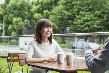 A young couple who talks happily on the cafe terrace