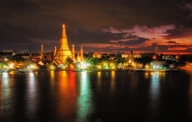 Wat Arun,the temple of dawn. famous landmark temple on Chaopraya River. Dramatic sunset twilight with bokeh lights at Bangkok,Thailand