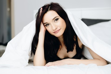 Beautiful young brunette woman relaxing and resting in bed