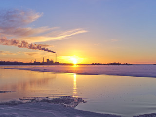 Beuatiful seaside winter sunset with a smoking factory chimney. Urban nature background.
