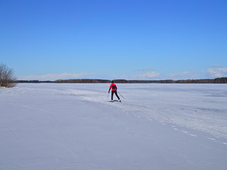 Cross country skier skiing on a frozen lake. Winter sports.