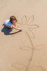 enfant dessinant sur la sable