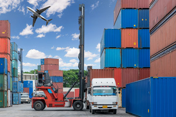 Forklift handling container box loading at docks with truck and airplane flying above for Logistic Import Export concept.