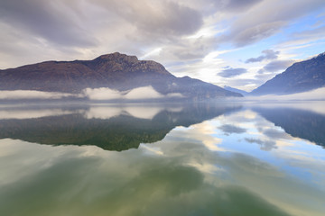 Mountains reflected in Lake Mezzola at dawn shrouded by mist, Verceia, Chiavenna Valley, Lombardy, Italy, Europe