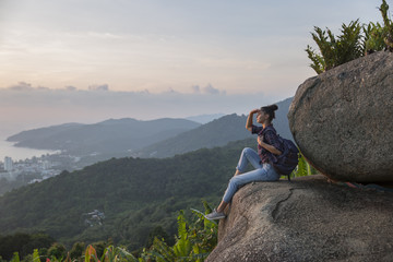 Hipster young girl with backpack enjoying sunset on peak mountain. Tourist traveler on background valley landscape view mockup.