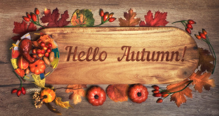 """Blackboard with text """"Hello Autumn""""with Fall decorations on wood. Top view, toned image."""