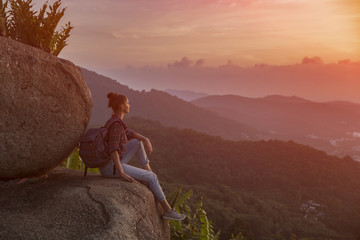 Hipster young girl with backpack enjoying sunset on peak mountain. Tourist traveler on background valley landscape view mockup. Toned, instagram vintage filter.