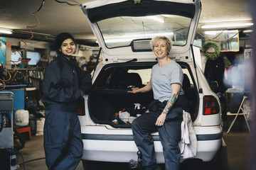 Portrait of smiling female mechanics with open car trunk at auto repair shop