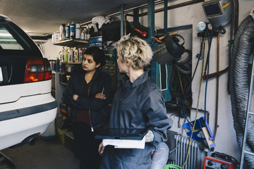 Female mechanic with customer examining car at auto repair shop