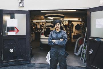 Portrait of confident female mechanic standing at entrance of auto repair shop