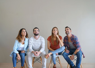 Young adults sitting on chairs and looking up, isolated