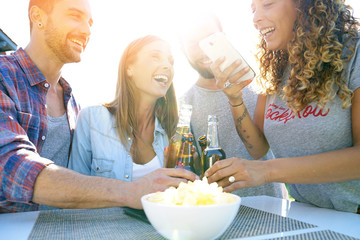 Group of friends havinga drink and using smartphone
