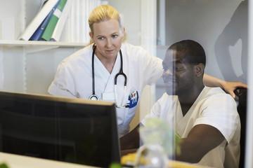 Male and female nurses using desktop computer in hospital