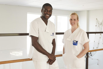 Portrait of happy male and female nurses standing against railing at hospital corridor