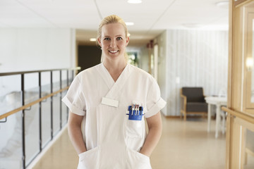 Portrait of happy female nurse standing with hands in pockets at hospital corridor