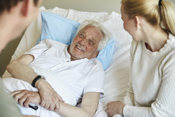 Happy senior man talking to couple while reclining on bed in hospital ward