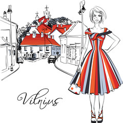 Vector color hand drawing. Cute beautiful fashion girl in summer dress on typical street in Old Town of Vilnius, Lithuania.