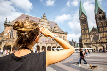 Young woman tourist enjoying great view on the city hall building and church in the centre of Bremen, Hamburg