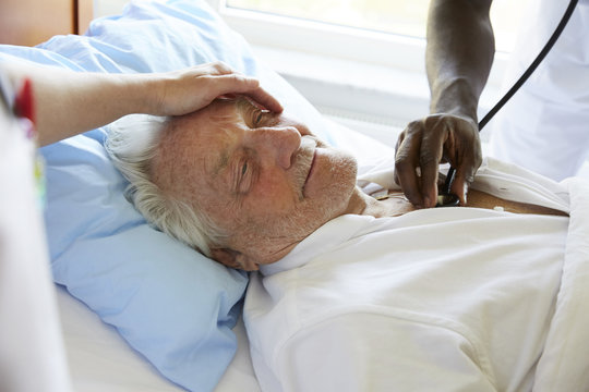 Cropped image of female nurse consoling senior man while male colleague examining with stethoscope in hospital ward