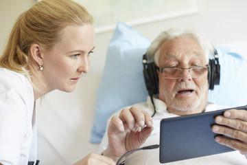 Female nurse assisting senior man in using digital tablet on hospital bed
