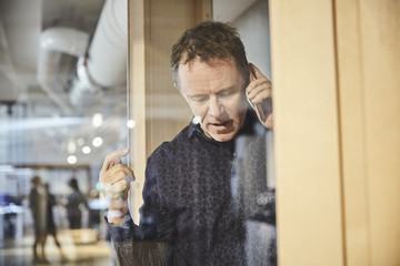 Mature businessman talking on mobile phone seen from glass at office