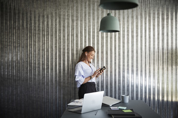 Smiling mature businesswoman using mobile phone while standing against corrugated iron wall at creative office