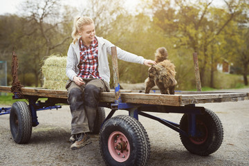 Smiling teenage girl stroking cat while sitting on old-fashioned trailer