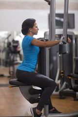 Bodybuilding. woman exercising in gym with exercise-machine arms back and shoulders.