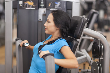 Bodybuilding. woman exercising in gym with exercise-machine arms back and shoulders
