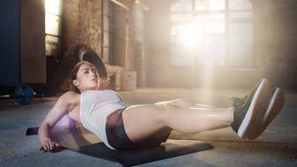 Athletic Beautiful Woman Does Crunches / Sit Ups /  Abdominal Exercises as Part of Her Cross Fitness, Bodybuilding Gym Training Routine.