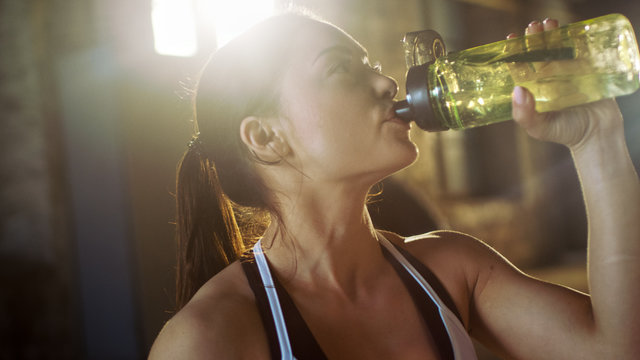 Strong Athletic Woman Drinks From a Water Bottle After Exhausting Cross Fitness Bodybuilding Training at Her Favourite Gym.