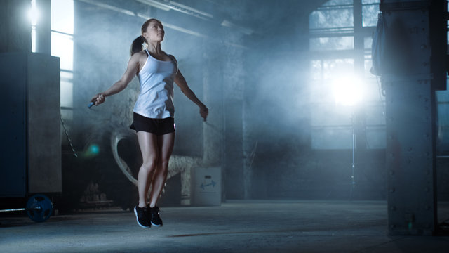 Athletic Beautiful Woman Exercises with Jump / Skipping Rope in a Gym. She's Covered in Sweat from Her Intense Cross Fitness Training. Dark atmosphere.