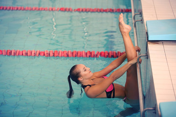 A female swimmer in indoor sport swimming pool. girl in pink sweimsuit training