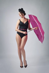 Woman in black bikini with umbrella .