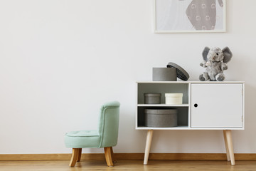 Green chair next to white shelf