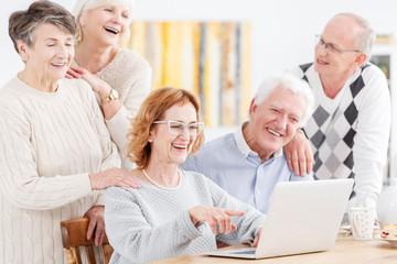 Elderly people looking at laptop