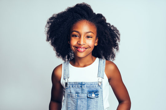 Smiling young African girl wearing dungarees against a gray back