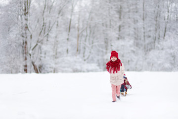 Two funny little girls having fun with a sleight in beautiful winter park. Cute children playing in a snow.