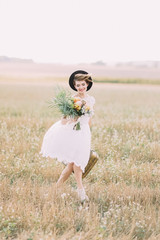 The vintage dressed bride is walking in the spring field. She is holding the colourful bouquet and carrying the retro suitcase.