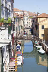 Scenic Rio Priuli, Cannaregio, Venice, Italy with moored boats and reflections. This is a tranquil back canal with colorful historic architecture