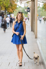 young woman walks with a pug along shop windows