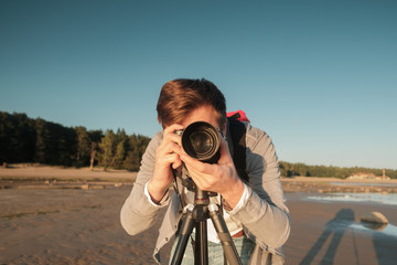 Young caucasian man making photo of landscape on seaside.