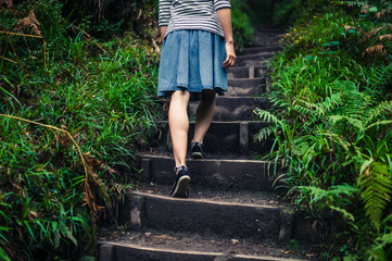 Woman walking up steps in the forest