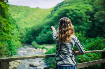 Woman on bridge in forest pointing