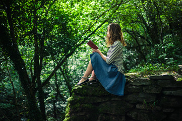 Woman reading book on wall in forest