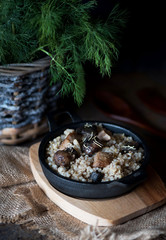 Barley porridge with forest mushrooms and meat in cast iron.